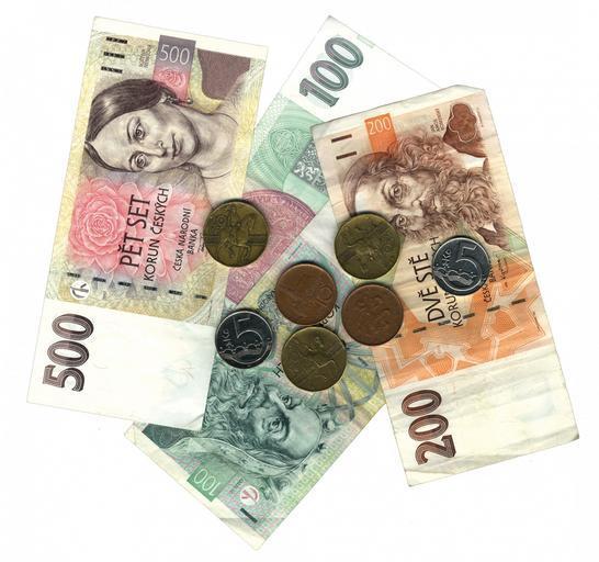 České peníze, dvoustovka, dvě stovky, pětistovka a drobné tři dvacetikoruny a dvě deseti koruny a dvě pětikoruny na bílém stole.
