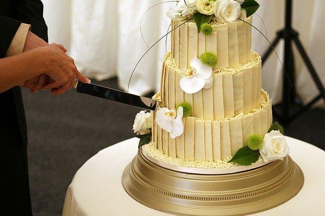 velký třípatrový dort ozdobený krémovými orchidejemi a růžemi, vše v krémové barvě, právě jej novomanželé krájí
