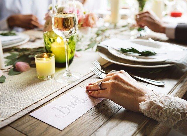 svatební hostina, nevěsta sedí u stolu, jde vidět ruka, která drží nápis bridge, dále je tam talíř, příbory, svíčka, sklenice a další věci
